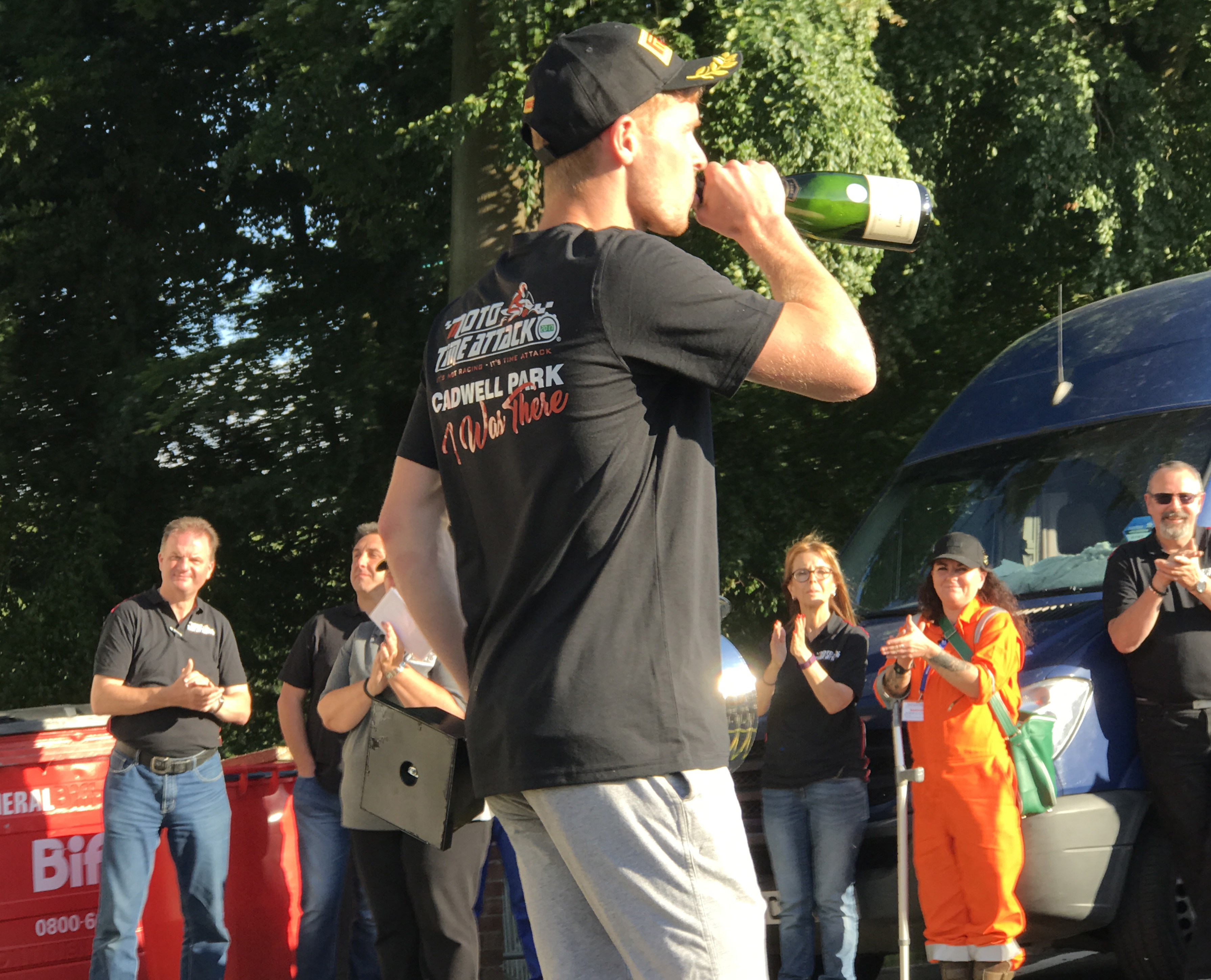 Tom Neave drinks champagne after Moto Time Attack win
